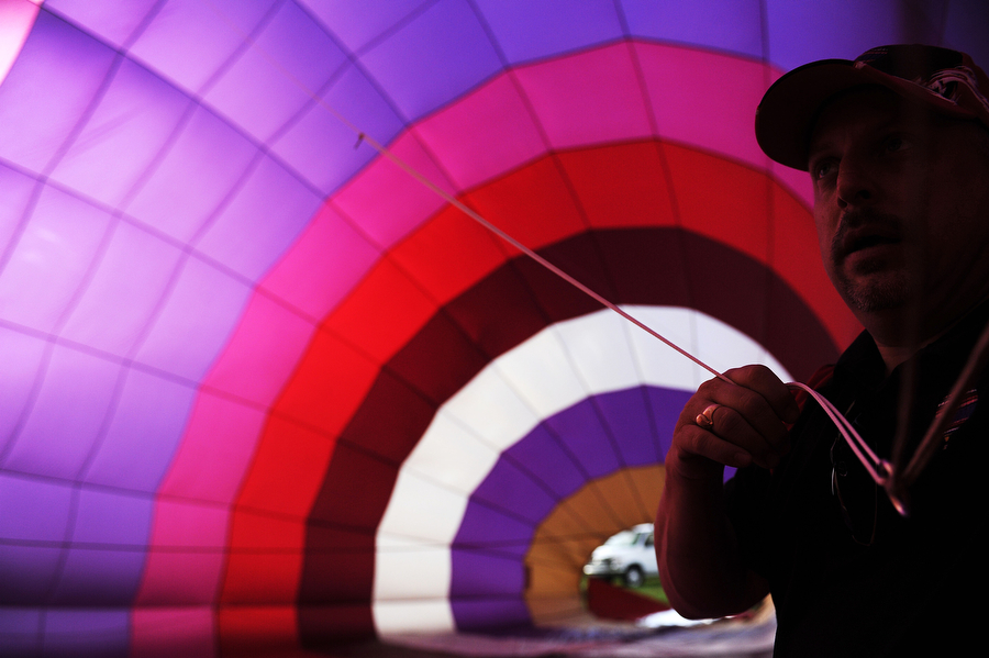 Pilot Wayne Fortney takes a look inside his balloon, Rosie, as it is filled with air in preparation for a ride during Lexington's 17th Annual Balloon Rally on Friday, July 5, 2013, on the parade grounds at the Virginia Military Institute. The balloon launches continue in the early morning on July 6.