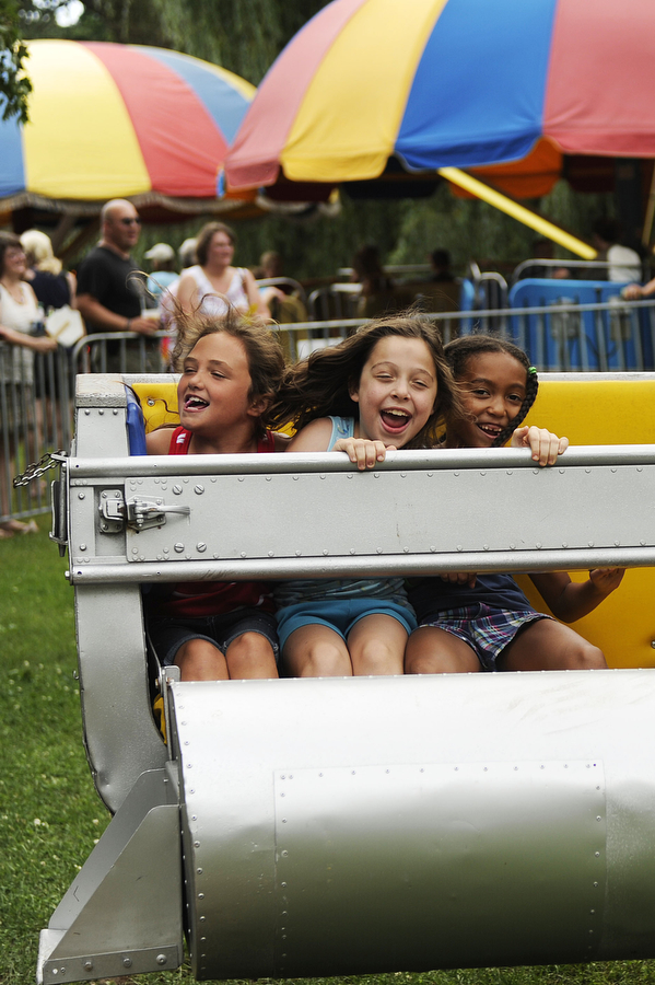 Madison Rutledge, 8, Emberly Jordan, 8, and Anaya Green, 7, (left to right), laugh while they ride a carnival ride during America's Birthday Celebration on Thursday, July 4, 2013, in Gypsy Hill Park.