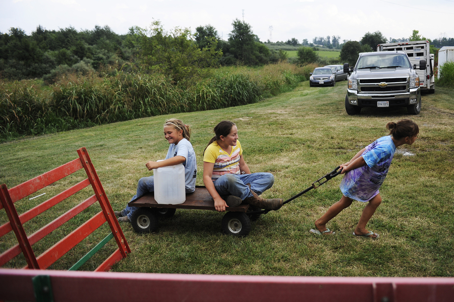 Montana Deming, 6, pulls sister Cheyenne Deming, 9 (left) and Makayla Talley, 10 (right) on Tuesday, August 6, 2013, during the Augusta County Fair at Expoland in Fishersville. Tuesday was the first day of the fair, which will continue through Saturday.