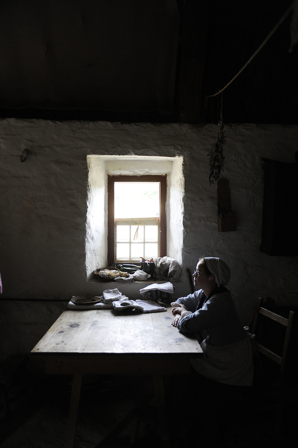 Employee Lindsey Bonsall sits down at a table inside the house at the Irish farm at the Frontier Culture Museum on Saturday, August 3, 2013, in Staunton.