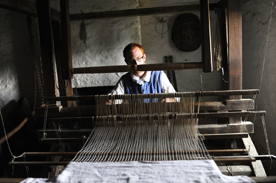 Employee Robby Keller works on the loom inside the house at the Irish farm at the Frontier Culture Museum on Saturday, August 3, 2013, in Staunton.