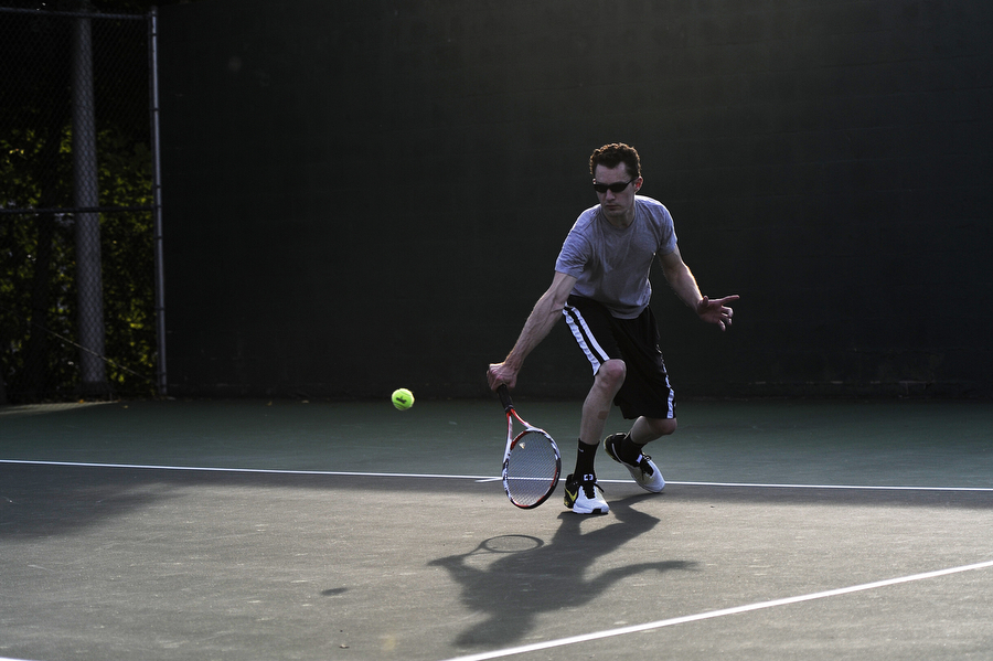 John Egnor hits a backhand return during the men's single open semi-finals at the Augusta Health/News Leader Tennis Tournament on Friday, Augusta 2, 2013, at Mary Baldwin College in Staunton.