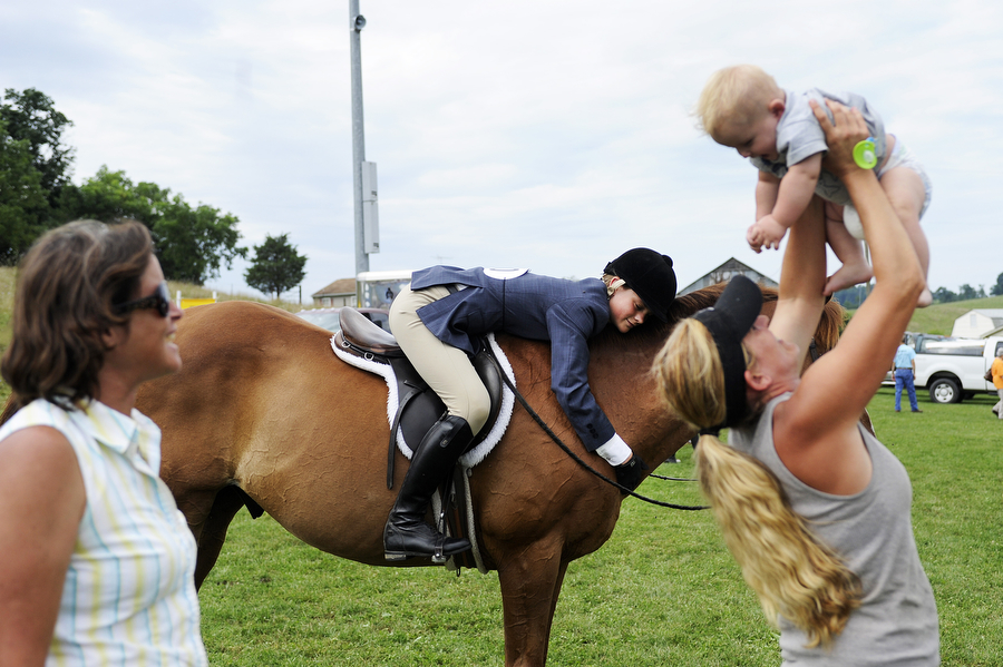 Eden Lange, 14, lays on her horse as Anita Warmington watches Megan Canavan play with her 8-month old son, Codey Reese, during the Middlebrook Ruritan Horse Show on Saturday, August 3, 2013, in Middlebrook.