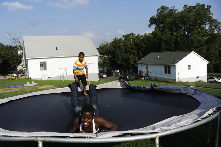 Rik'avian Carey, 11, lands after taking a big leap on a neighbor's trampoline as Dathan Brotherton, 8, watches on Monday, Sept. 9, 2013, in Staunton. The two are cousins and played on the train track and on the trampoline.
