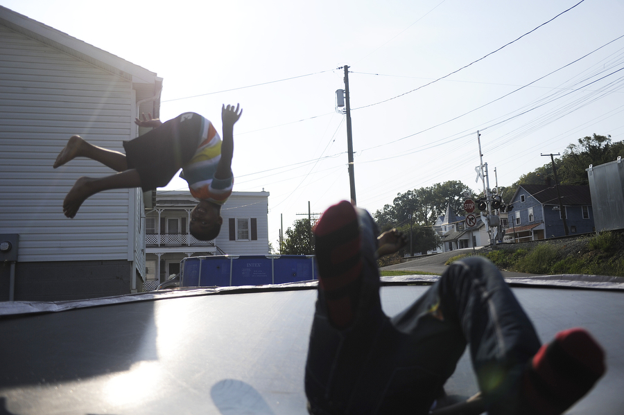 Dathan Brotherton, 8, and Rik'avian Carey, 11, take turns doing flips on a neighbor's trampoline on Monday, Sept. 9, 2013, in Staunton. The two are cousins and played on the train track and on the trampoline.