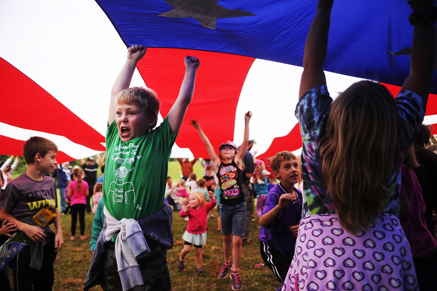 Children play under a large American flag as their parents hold it up during the kite festival on Saturday, Sept. 28, 2013, at Coyner Springs Park in Waynesboro. The event featured kite making, parachute races and face painting.