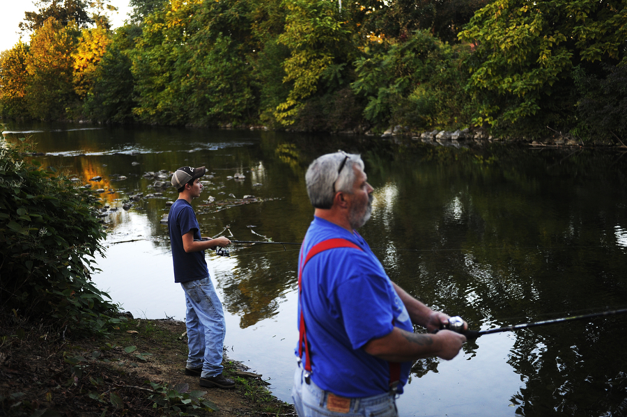 James Holmes and son Evan Holmes, 16, of Crimora fish along the South River off the Greenway on Tuesday, Sept. 25, 2013, in Waynesboro. The city of Waynesboro highlights the benefits of fishing in the South River in its tourism efforts, though only the trout in the river can be consumed. There is a consumption advisory on all other fish in the river, and a consumption limit on fish along the South Fork River.
