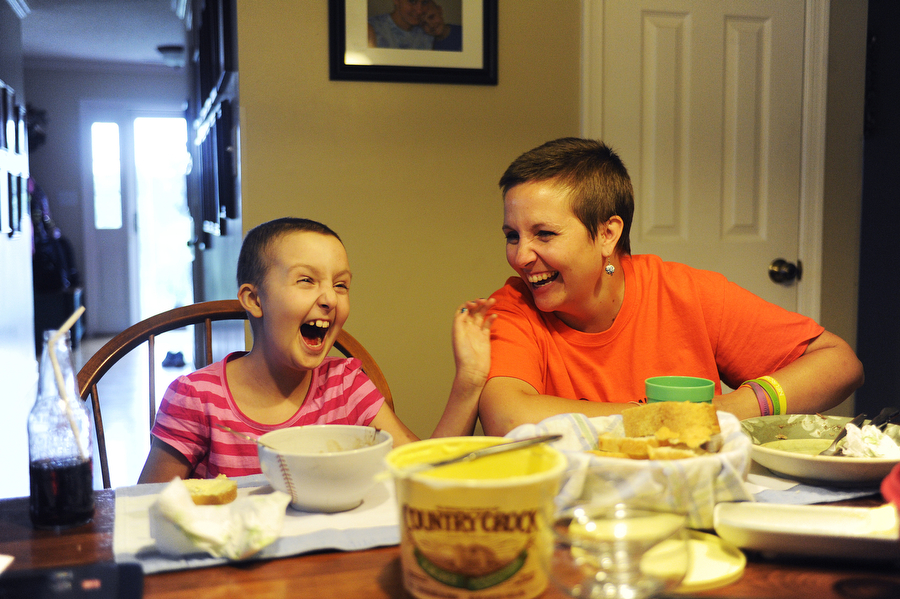 Norah laughs with her mother, Colleen, during dinner at home Aug. 20. During her treatment, Norah would have some better days than others, where she was lively, sarcastic and talkative. On other days, she was fatigued and would spend hours on the couch.
