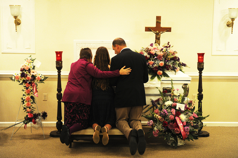 "The family kneels in front of Norah's casket. ""We've changed so much and lost so much,"" Colleen said."