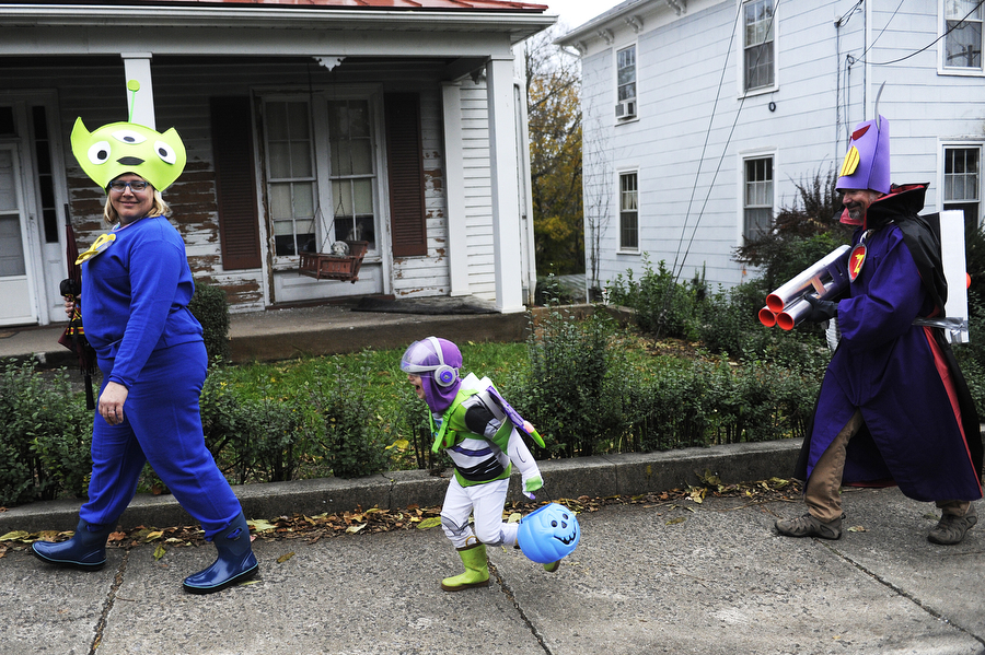 Donna, Arlo and Keith Ellingsworth head out to trick-or-treat dressed as 'Toy Story's' alien, Buzz Lightyear and Emperor Zurg during Halloween on Thursday, Oct. 31, 2013, in Staunton.