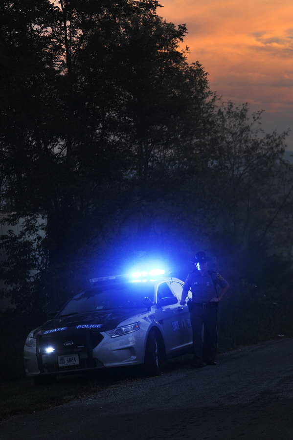 A state trooper stands by his vehicle to direct emergency vehicles responding to a house fire on Springfield Lane on Saturday, Oct. 19, 2013, in Staunton.