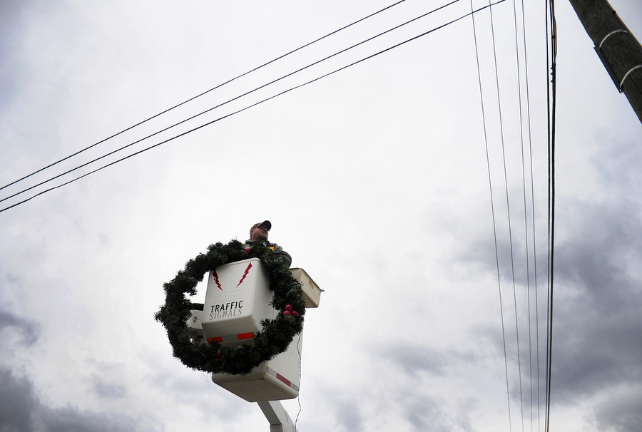 John Snyder, crew coordinator for Staunton Parks and Recreation Department, is raised in a cherry picker to hang a Christmas wreath on a post along Lee Jackson Highway on Tuesday, Nov. 12, 2013, in Staunton.