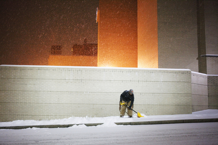 A boy shovels snow as it falls on Augusta Street on Feb. 12, 2014, in Staunton.