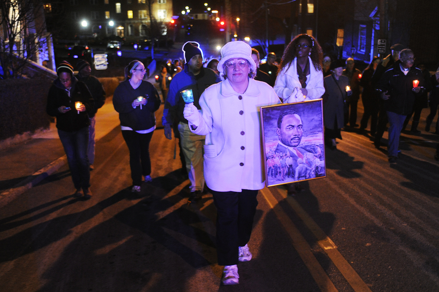 Toni Landram holds a portrait of the reverend as she walks during the Martin Luther King Jr. Candlelight March on Monday, Jan. 20, 2014, in front of Central United Methodist Church in Staunton. The march, which is followed by a memorial service, has been held for 23 years.
