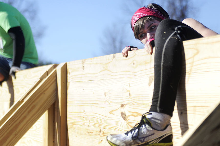 Runners scale a wooden wall during the Mad Anthony Mud Run on Saturday, Feb. 22, 2014, in Waynesboro. The 4.5-mile course included a multitude of obstacles, including a wooden wall, hay bales to scale and a muddy swamp pit.