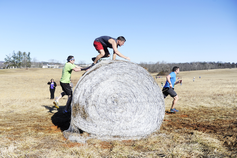 Runners scale a hay bale during the Mad Anthony Mud Run on Saturday, Feb. 22, 2014, in Waynesboro. The 4.5-mile course included a multitude of obstacles, including a wooden wall, hay bales to scale and a muddy swamp pit.