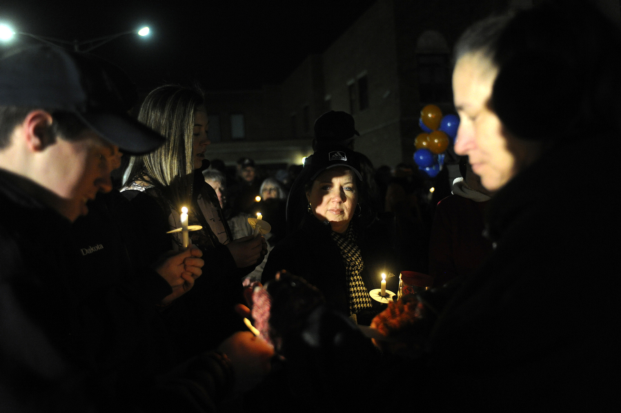 People light their candles before the candlelight vigil in the memory of Waynesboro Police Department reserve captain Kevin Quick on Saturday, Feb. 8, 2014, in Waynesboro. Quick served on the police force since 1990 and was last seen on Jan. 31. A body was found in Goochland County Thursday that was confirmed to be Quick. Three people were arrested and charged in connection with his death.