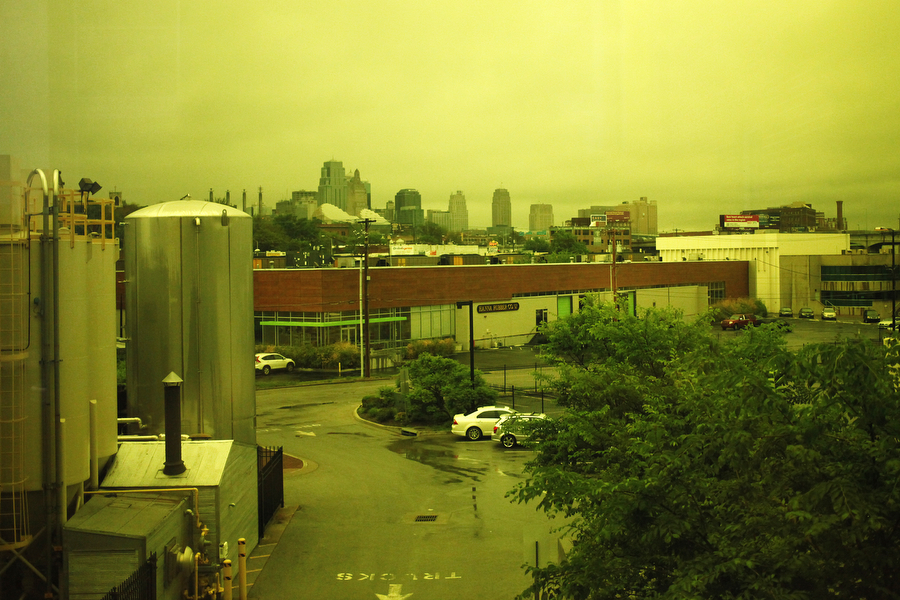 The Kansas City skyline appears yellow through a tinted window at Boulevard Brewery.