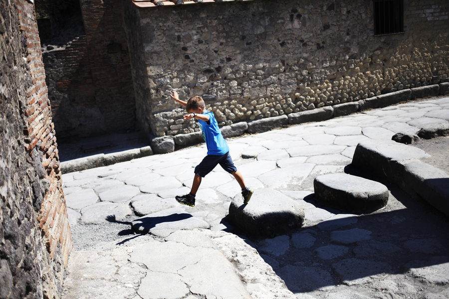 A child jumps across stones in the ruins of Pompei, the city destroyed by Vesuvius, on Tuesday, July 15, 2014.