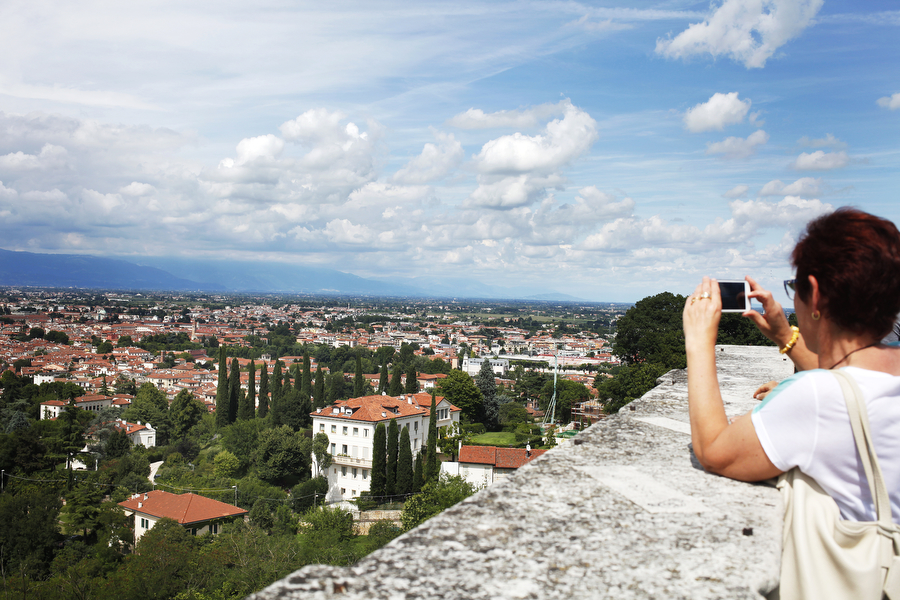 A woman photographs a panoramic view of Vicenza as seen from Monte Berico.