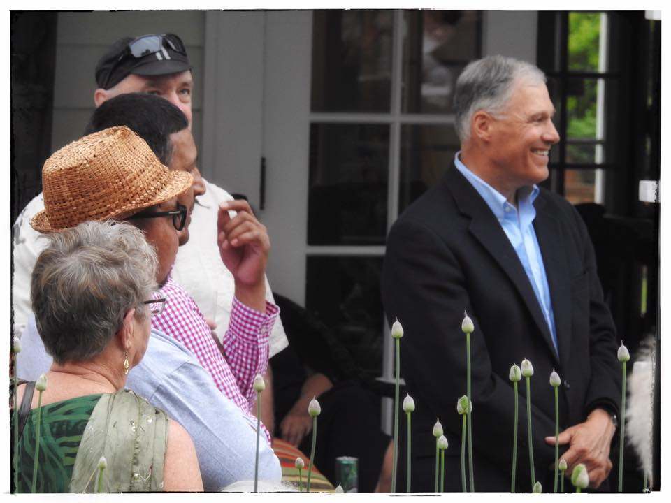 Washington State Governor Jay Inslee listens to a speaker during a re-election fundraiser in Bellingham. He is joined at left by Lummi Nation Business Council Chair Tim Ballew II. PHOTO: Tara Nelson