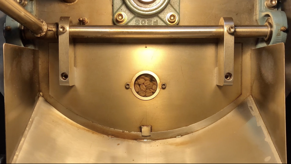 Roasting - Industrial Roaster with a master slow roaster at the wheel.
