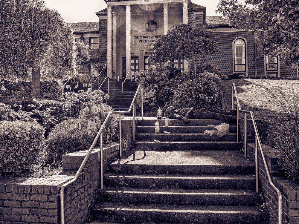 'My Friend' sleeps on the steps of the 8th Ave NE Church of Jesus Christ of Latter Day Saints on Sunday, May 21, 2017. Rhys Riddell/Tangle.Town