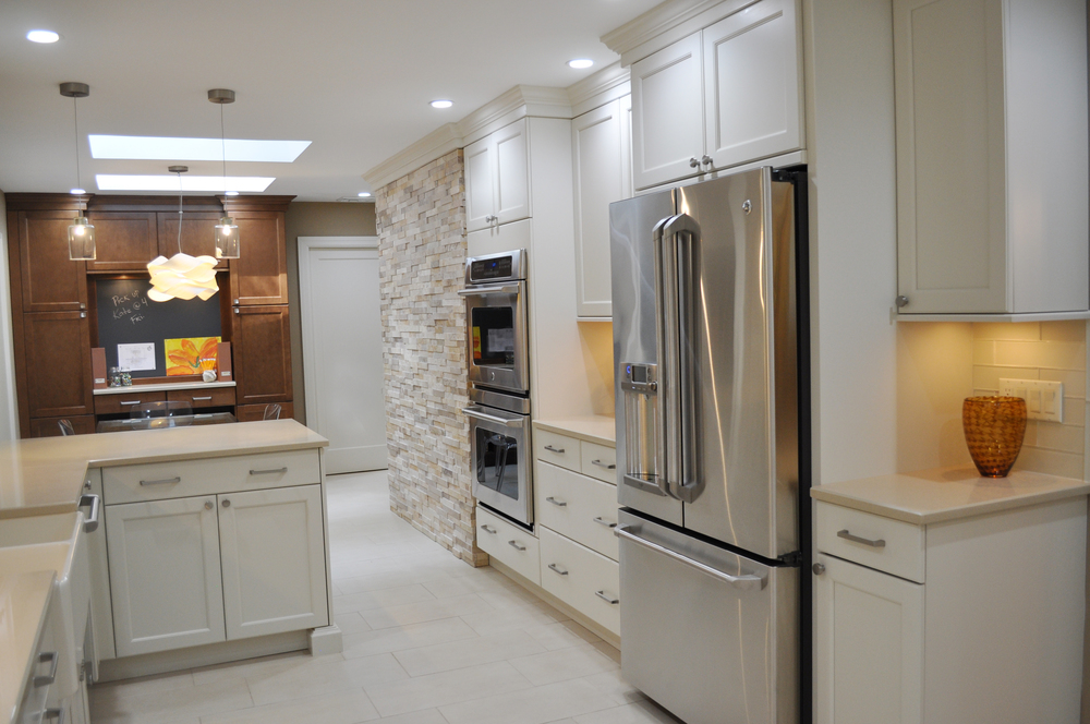 KAM DESIGN LLC_Kitchen Renovation_White Kitchen Cabinets_Satin Nickel Hardware_Stone Wall_Stainless Refrigerator_Quartz Kitchen Counters.jpg