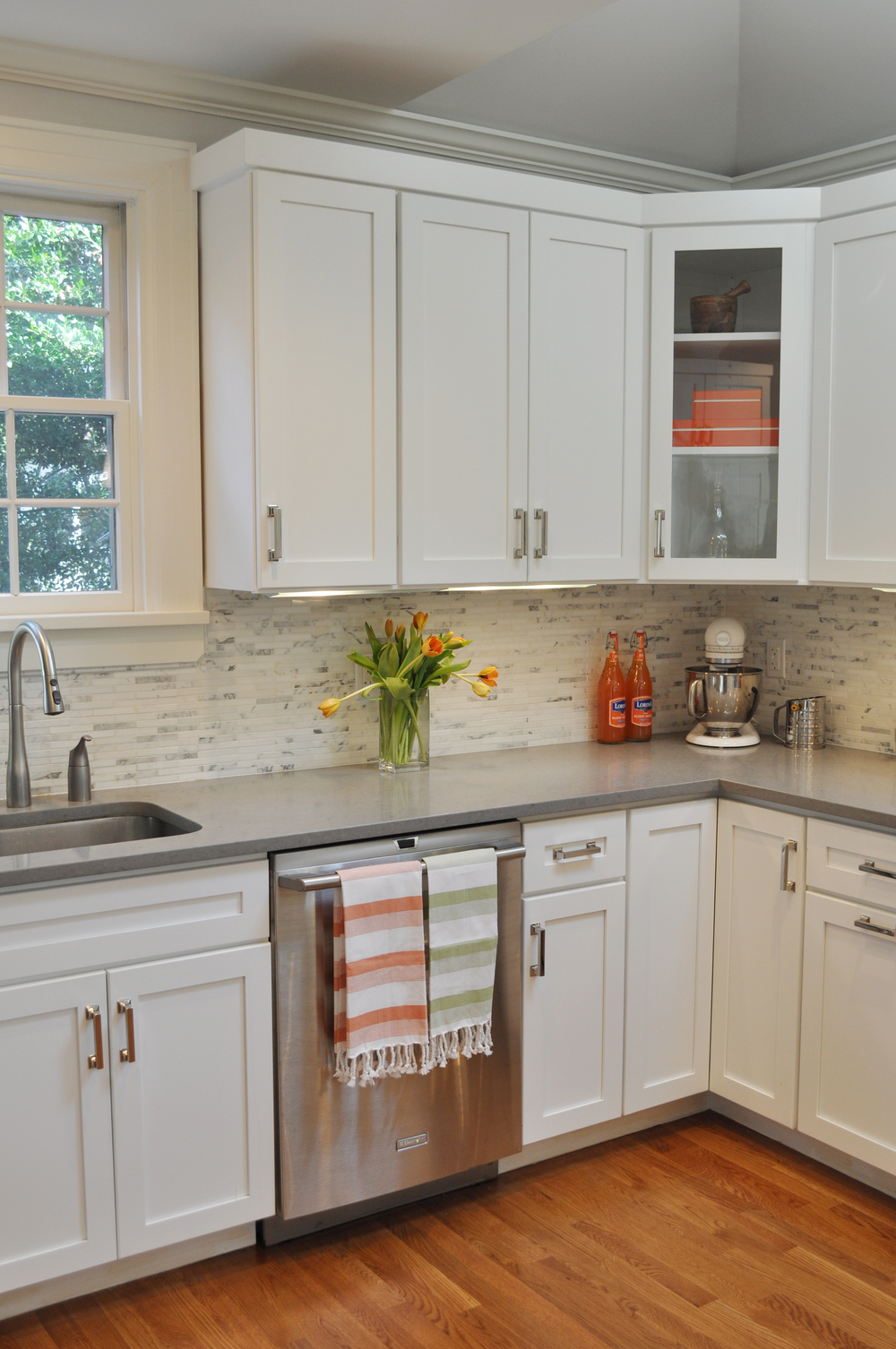 "CLASSIC WHITE KITCHEN, Larchmont, NY:  The existing kitchen space was crowded, functionally-impaired and uninspired.  The new kitchen is styled with white Shaker-style cabinets, Caesarstone ""cement-colored"" countertops for a bit of urban style and timeless Carrara marble backsplash tiles in a modern horizontal orientation for a fresh look fitting for the young family. The new peninsula is highly functional as it serves as the breakfast and homework area. The renovated space allows for extra natural light through new skylights and French doors to the outdoor patio, while hand-blown glass pendants and under-counter lighting provide interest and ambiance."