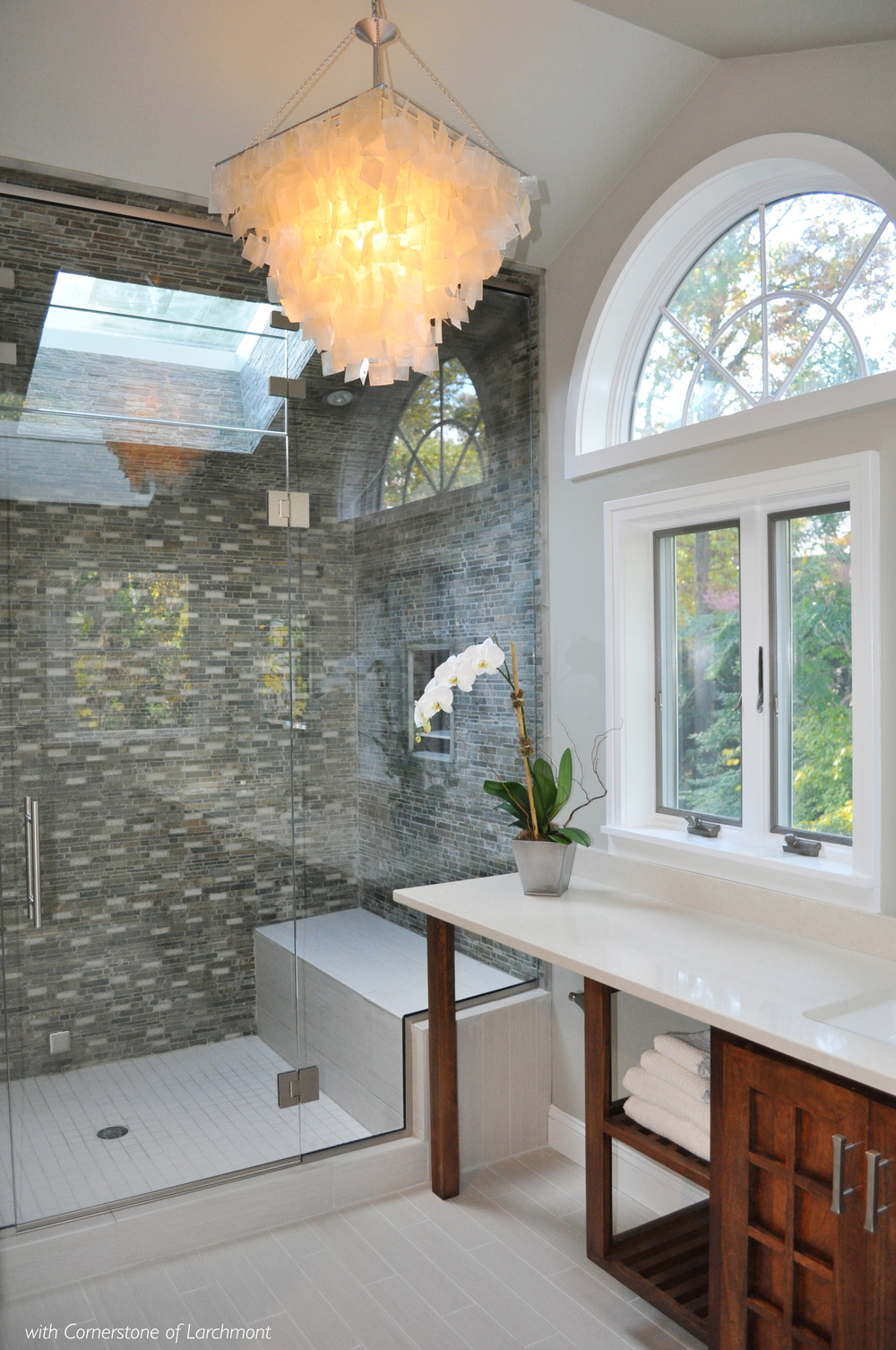 "ASIAN INSPIRED MASTER BATH RETREAT, Larchmont, NY: The master bath remodel is inspired by the homeowner's years in Asia. The luxurious space provides a spa-like retreat that connects with the outdoors. The renovation plan revamps the cramped and dysfunctional space creating separate and usable spaces. The total remodel adds two skylights and arranges new windows to maximize space and infuse the room with light. Porcelain ""metallized"" floor tile installed like wood planks and capiz shell chandelier introduce a sophisticated, contemporary twist to the Asian motif. A custom designed double-sink wood vanity allows for a make-up area, while a celedon slate and white glass tiled steam shower offers the ultimate in relaxation."
