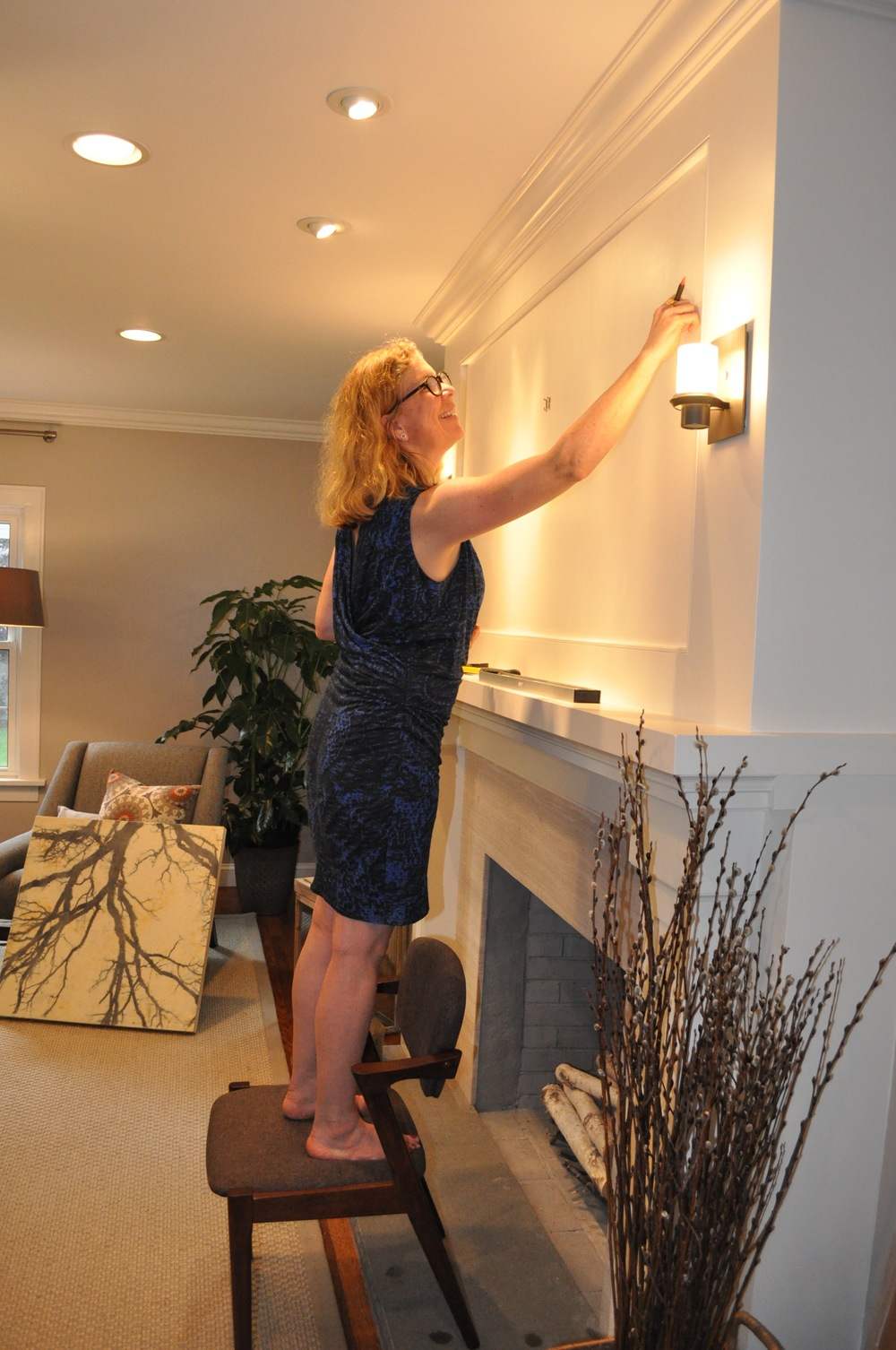 Kenise Barnes of Kenise Barnes Fine Art hangs artwork from her gallery.