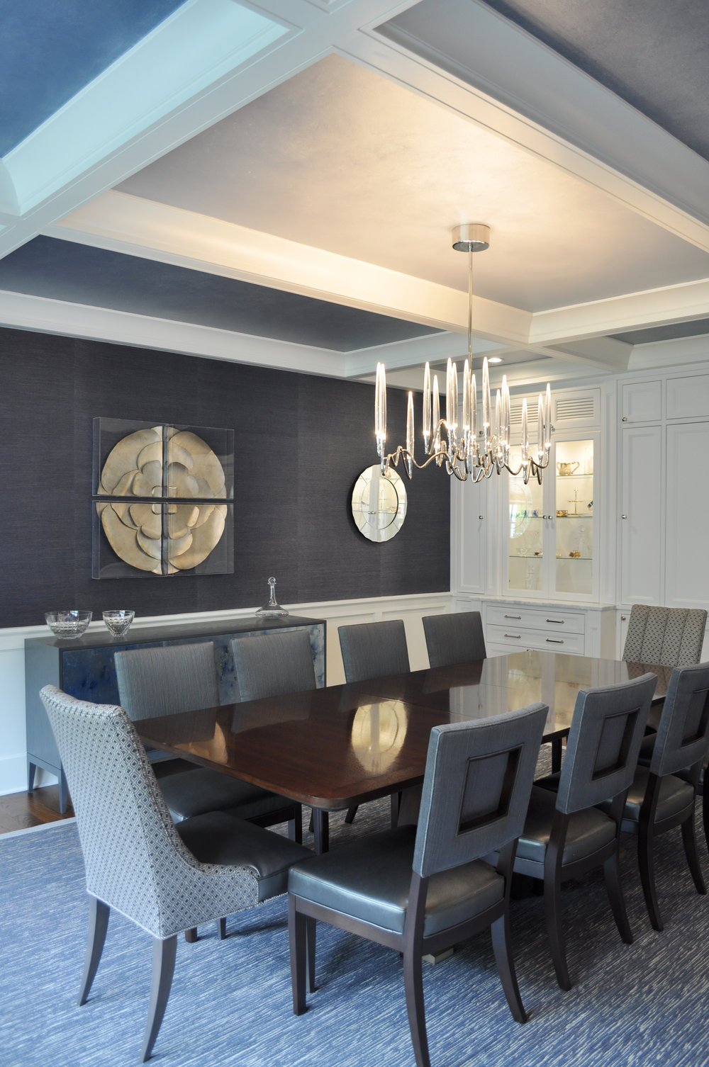 CELESTIAL NIGHT SKY TIMELESS DINING ROOM , New Rochelle, NY: The mood of this midnight blue dining room  is transporting and its style, refined and enduring. Custom-designed coffered ceiling, wainscoting and display cabinets with a built-in wet bar establish architectural interest in the large otherwise vacuous space.  An ombre design effect starts at the center of the room, where a pearlescent silver-blue faux paint finish on the center ground of the coffered ceiling is highlighted by the lighted crystals of the curving organic-shaped Italian chandelier. The ceiling grounds surrounding this  center ground are a darker blue-silver that lead gracefully into the dark blue grasscloth wall covering. A contemporary blue antiqued mirror sideboard reminds one of a cloudy night sky, while the sculptural four-piece silver medallion art encased in acrylic clear boxes plays with the notion of a full moon. The wood detail cut-out back of the tailored dining chairs repeat the box motif from the ceiling, artwork and wainscoting, while the upholstery marries a textured gray-blue striated back fabric with a subtle metallic gray leather seat fabric. The warm walnut wood dining table with embellished champagne metallic feet sit on an area rug reminiscent of shooting stars as its silver flecks intertwine with midnight blue.