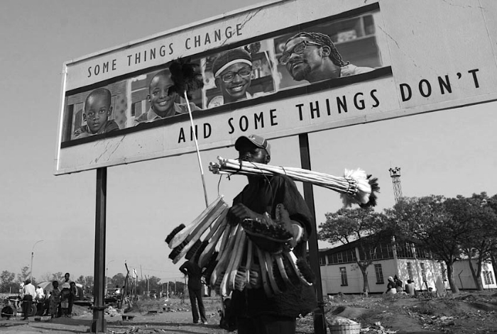 A street vendor selling brushes walks past a billboard in Harare, Zimbabwe, Oct. 9, 2007.