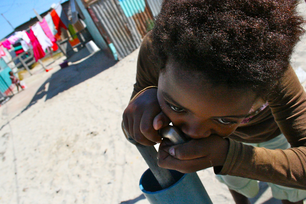 Lolitha Setyala, 10, drinks clean water from a spigot. But in other sections of Khayelitsha, children exposed to dirty water often complain about rashes on the backs of their hands and on parts of their faces.