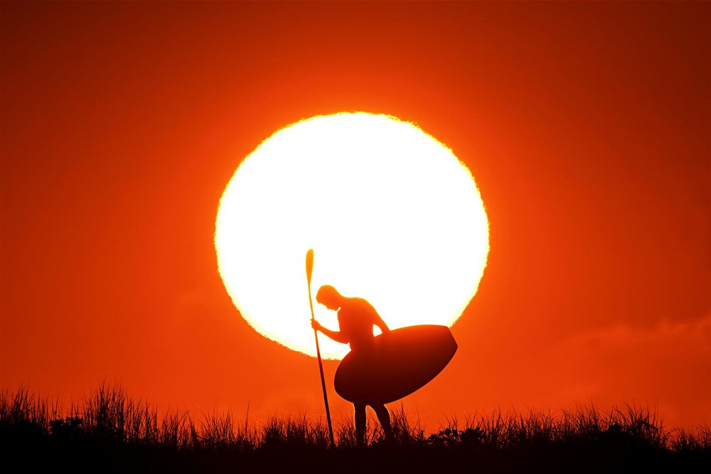 sunrise silhouette with lifesaver waterman Jayden Jensen