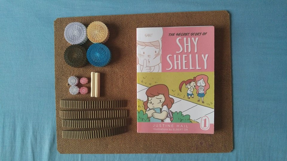 Art spread. Preparing rolls of corrugated-color paper for the kokoru (available in NBS) and a limited edition paper back copy of Shy Shelly.