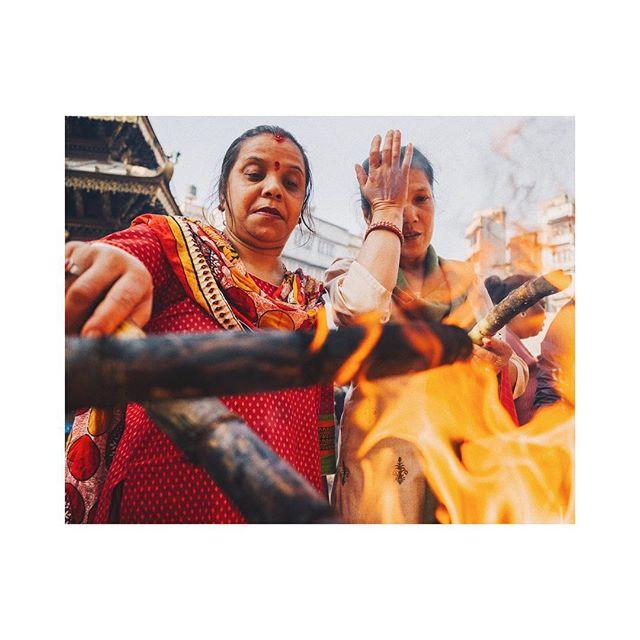 two women stoke a fire pit during the dashain festival, kathmandu, nepal. #fujifeed
