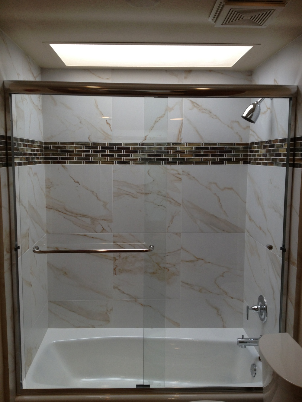 Beautifully tiled guest shower/tub with skylight