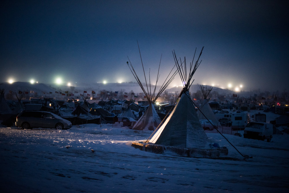 Blizzard conditions help the DAPL security lights illuminate the Oceti Sakowin camp at the Standing Rock Sioux Nation. December 4, 2016