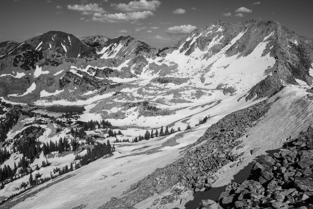 Snowpack on July 3 in the Red Pine cirque. White Baldy peak towers above Red Pine Lake and granite talus slopes. Big Cottonwood Canyon, Lone Peak Wilderness, Utah.