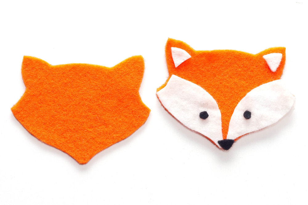 Step 1. Draw out the shape of a fox head onto paper to use as a template. Then trace around the template onto the orange felt and cut out twice. From the white felt, cut out the two inner ear shapes, and the two shapes for the sides of the face. Finally, from the black felt cut out two small circles for the eyes and a small triangle for the nose.
