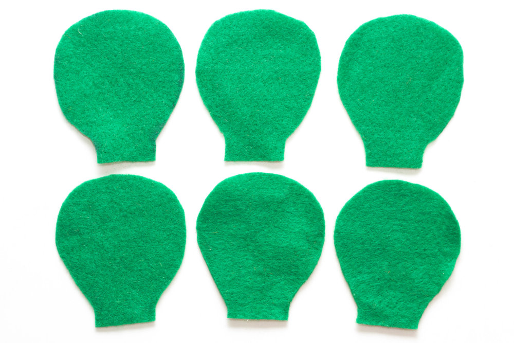 Step 1 Draw the shape seen in the photo above onto the green felt six times and cut these shapes out (the shape should be approximately 10cm high). These will form the cactus. It helps to make a template first so all of the shapes are identical.