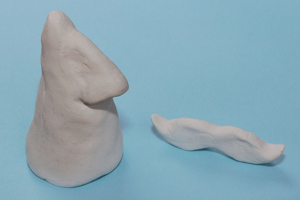 Step 1 Take a large section of the air dry clay and make a cone shape. Then mould a smaller nose shape and attach the two together, smoothing the edges so that it doesn't come apart. Take another smaller piece of clay and mould a moustache shape. Leave all the pieces to dry overnight.