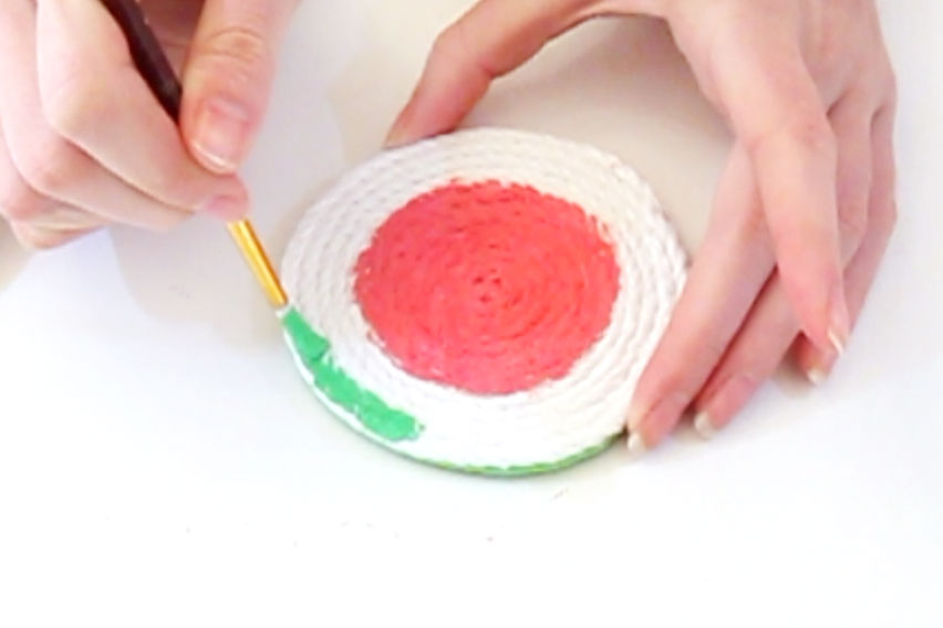 Step 3 Mix the red and white paint together until you have the colour for the centre of the watermelon. Paint a circle in the middle of the coaster with this paint. Then paint around the edge of the rope with the green paint, leaving a small white line in-between the two colours. Leave to dry. Once the red paint is dry, paint some small black dots over the top of it to create the watermelon seeds.