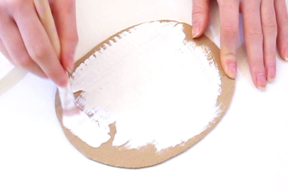 Step 2  Cut out an oval shape from the cardboard, approximately 18cm by 14cm. Paint this piece of cardboard white and leave to dry.
