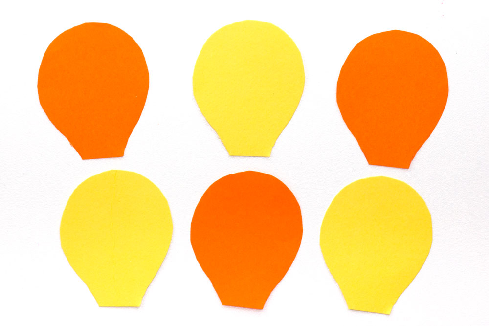 Step 1 Cut out 6 hot air balloon shapes from the coloured paper. I decided to make mine two different colours, however you could create a multicoloured hot air balloon! Try to cut out the shapes all at the same time to ensure they are all the same size.