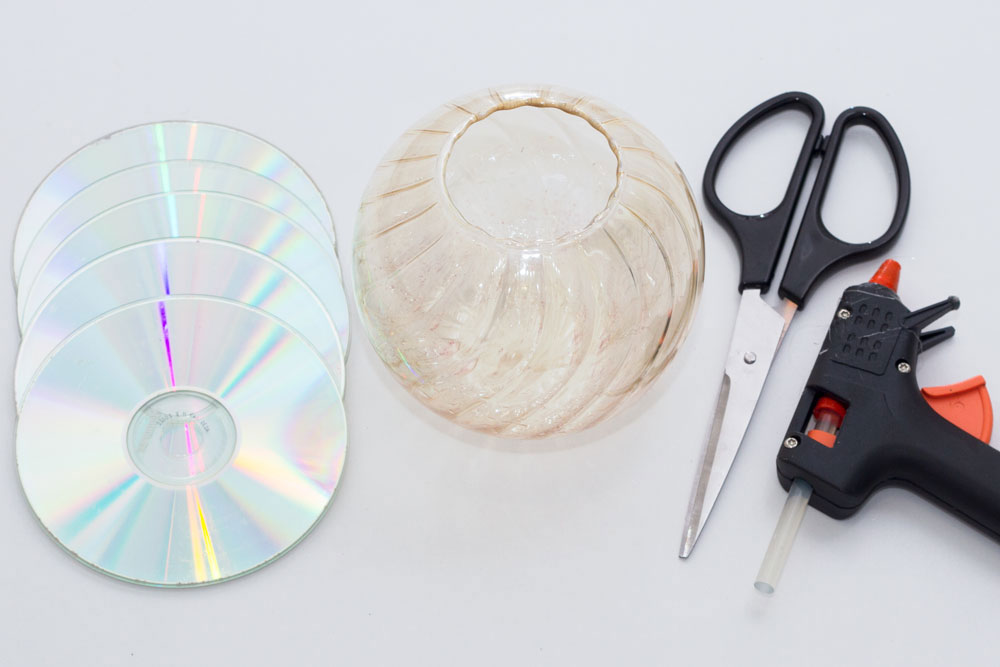 You will need: CDs (approximately 5) Scissors Glue gun Spherical glass/vase - I bought mine in a charity shop, however I have seen them in most home stores and lots of places online!