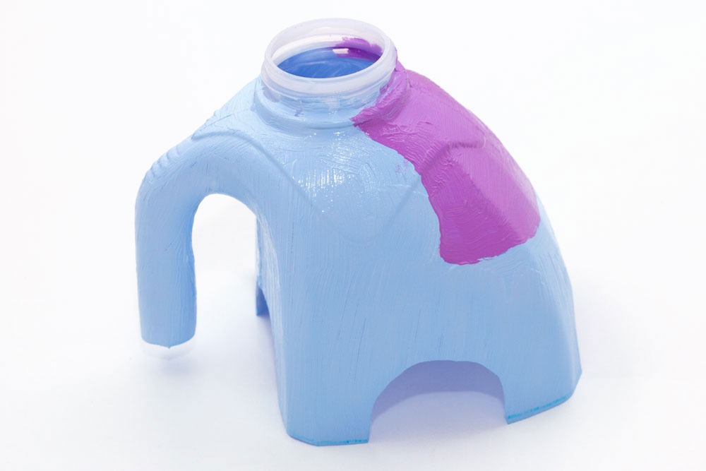 Step 2  Paint the milk bottle. I decided to paint the elephant light blue with a purple sheet on its back. It is best to take the lid off of the milk bottle first so you don't accidentally get paint on it.