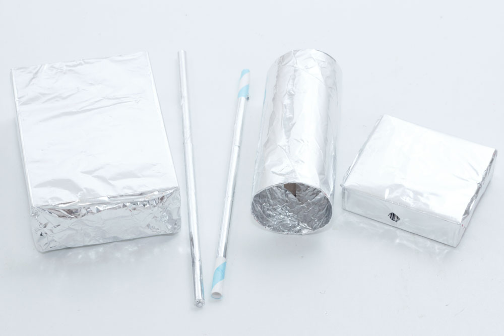 Step 2  Cover the boxes, straws and toilet roll tube in tin foil, gluing and taping where necessary. Once you have covered the boxes, carefully push through the foil where the holes are as you can see in the small box in the photo above.