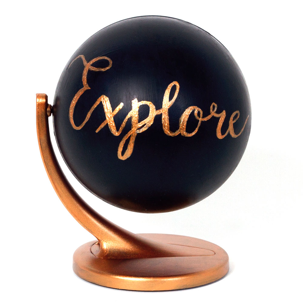 Step 3  With the gold or copper pen (or use the paint if you don't have a pen) carefully write the word of your choice onto the black globe. I wrote explore in a swirly font! If you are using paint you might have to do a few coats so it stands out on the black.